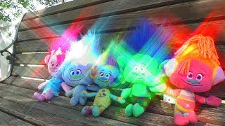 Trolls and funny kid Yulya playing outdoors with toys