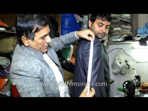 Indian tailor at work, measuring clients for fit-outs