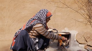 Indian woman wearing salwar suit is making roti in chulah for her family