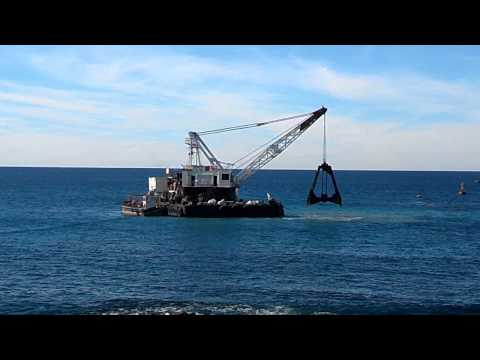 Dredging close to shore of the Pacific sea.