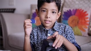 An Indian kid playing with a digital camera and taking out memory card from the slot