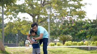 Handsome Indian father teaching his son how to play badminton - outdoor games