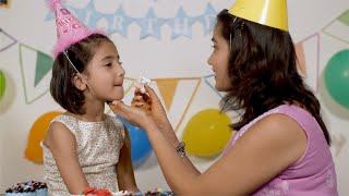 Birthday Party - An Indian mother enjoying and feeding cake to her daughter