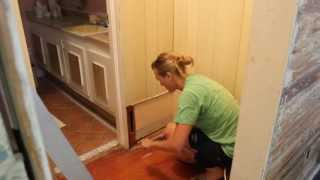 using a pry bar to remove paneling and nails