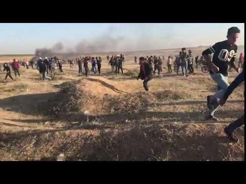 Gazans run away from border after Israeli army fires tear gas.