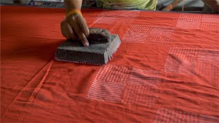 A worker block printing red fabric with the white design