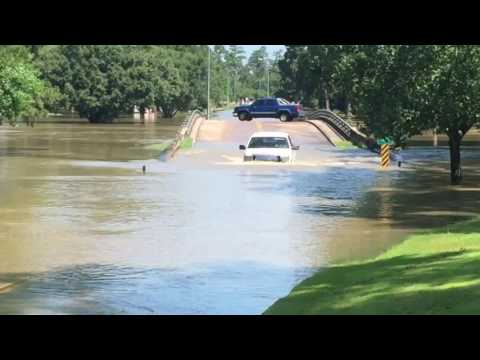 Trucks Driving Through The Flood Waters In Spring Tx At Willow