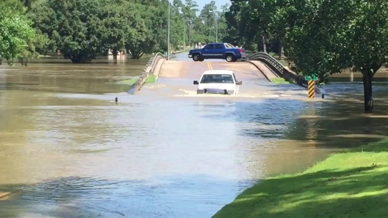 Trucks Driving Through Houston Texas Flood Waters Of Willow Creek At