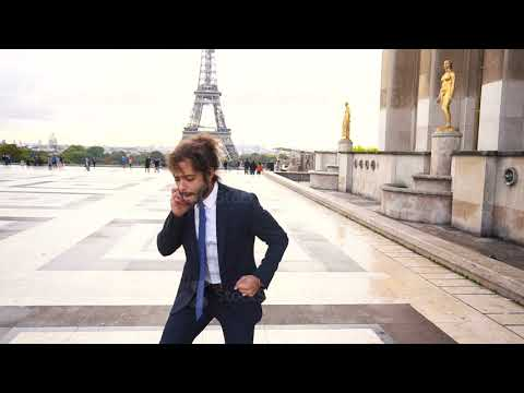 Jocund mulatto guy raving near Eiffel Tower and calling friend by phone in slow motion