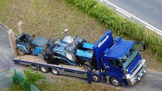 急斜面の狭い道路に重機回送車を止めて、現場で舗装作業を終えた アスファルト...
