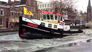 Sleepboot breekt door het ijs op de Vliet in Leidschendam