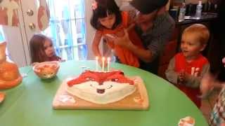 Blowing out her 3 candles on her birthday cake