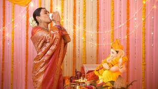 Young Indian woman dressed in traditional saree and blowing the sankha (counch shell) for Ganesh pooja