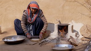 Desi Indian woman preparing roti / Indian bread in chulha for her family
