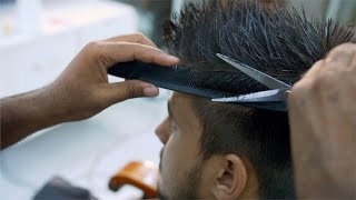 Close-up of barber cutting clients hair at barbershop