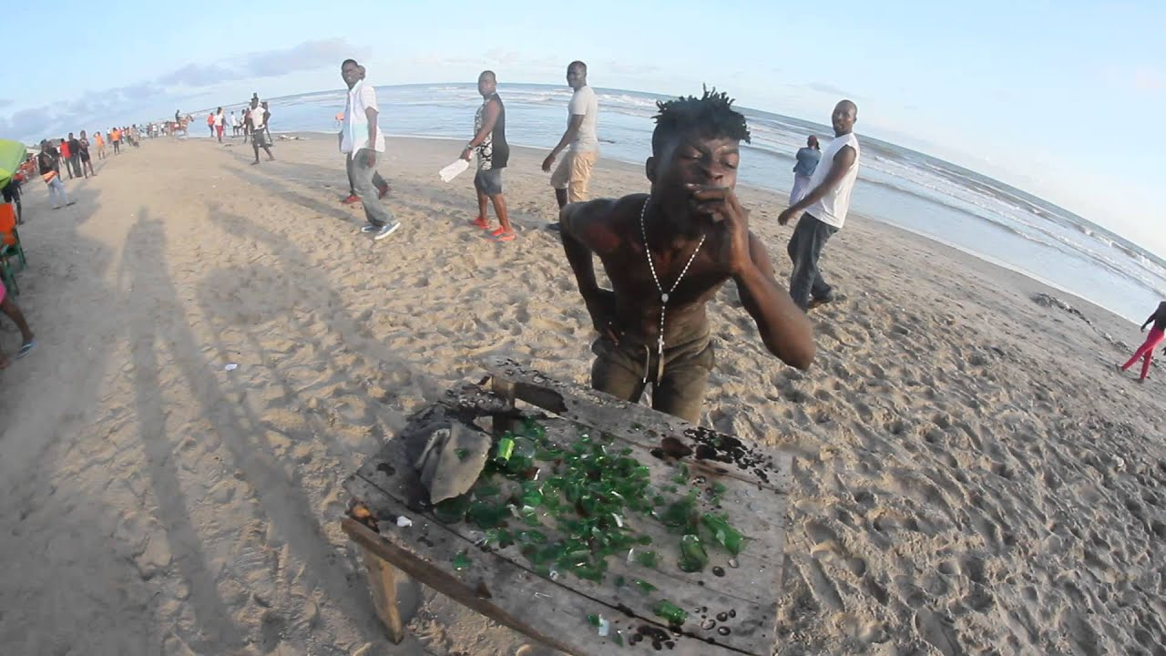 Download Ghanaian Guy eating broken pieces of bottle and spitting it out at the beach