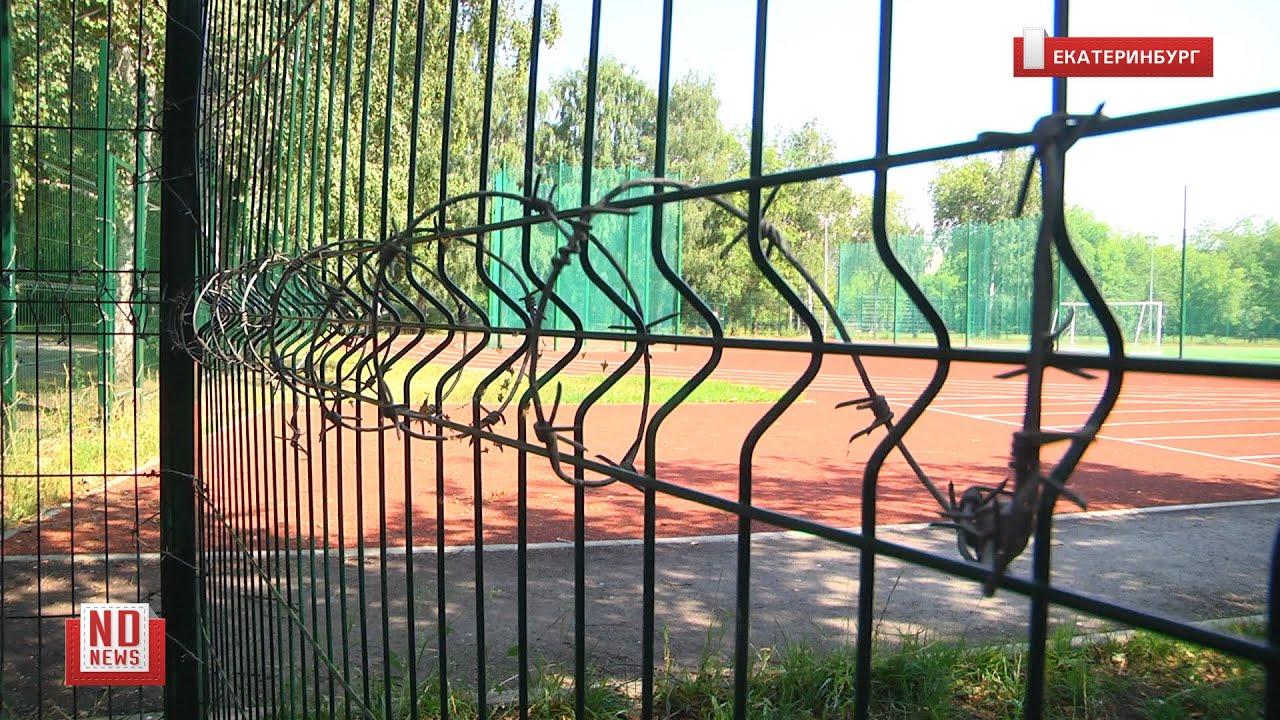 Колючая проволока на заборе школьного стадиона