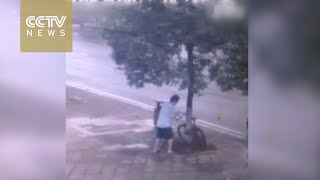 Surveillance camera captures man chopping down tree to steal bike(Surveillance video in Changsha city, central China's Hunan Province, has captured a man felling a tree with a chainsaw in order to steal a bicycle locked to it., 2016-08-10T02:19:28.000Z)