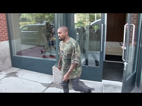 Kanye West runs to his car wearing camouflage in New York