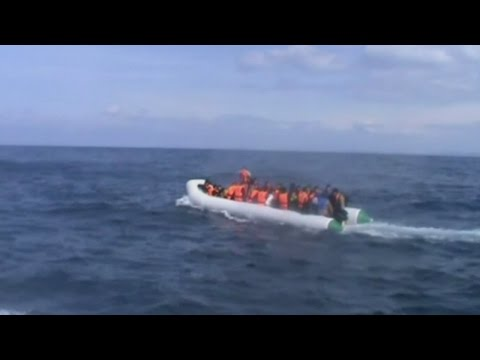 Afghan migrants hold baby up to Turkish coastguard personnel