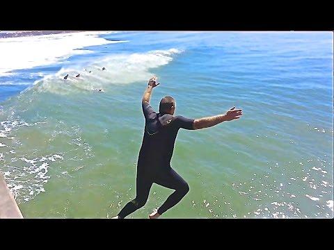 Surfer Jumps Off Huntington Beach Pier CA. 3-8-2016 During High Surf