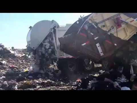 Garbage Trucks Unloading At The Dump