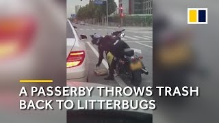 A passerby throws trash back into a litterbug's car