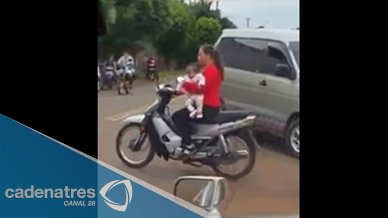 video mujer conduce motocicleta con su beb en brazos. Black Bedroom Furniture Sets. Home Design Ideas