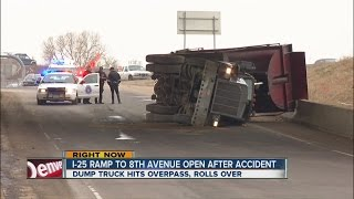Dump truck hits I-25 overpass, rolls over
