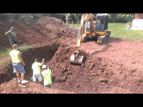 Excavator earth mover digging in ground pool track