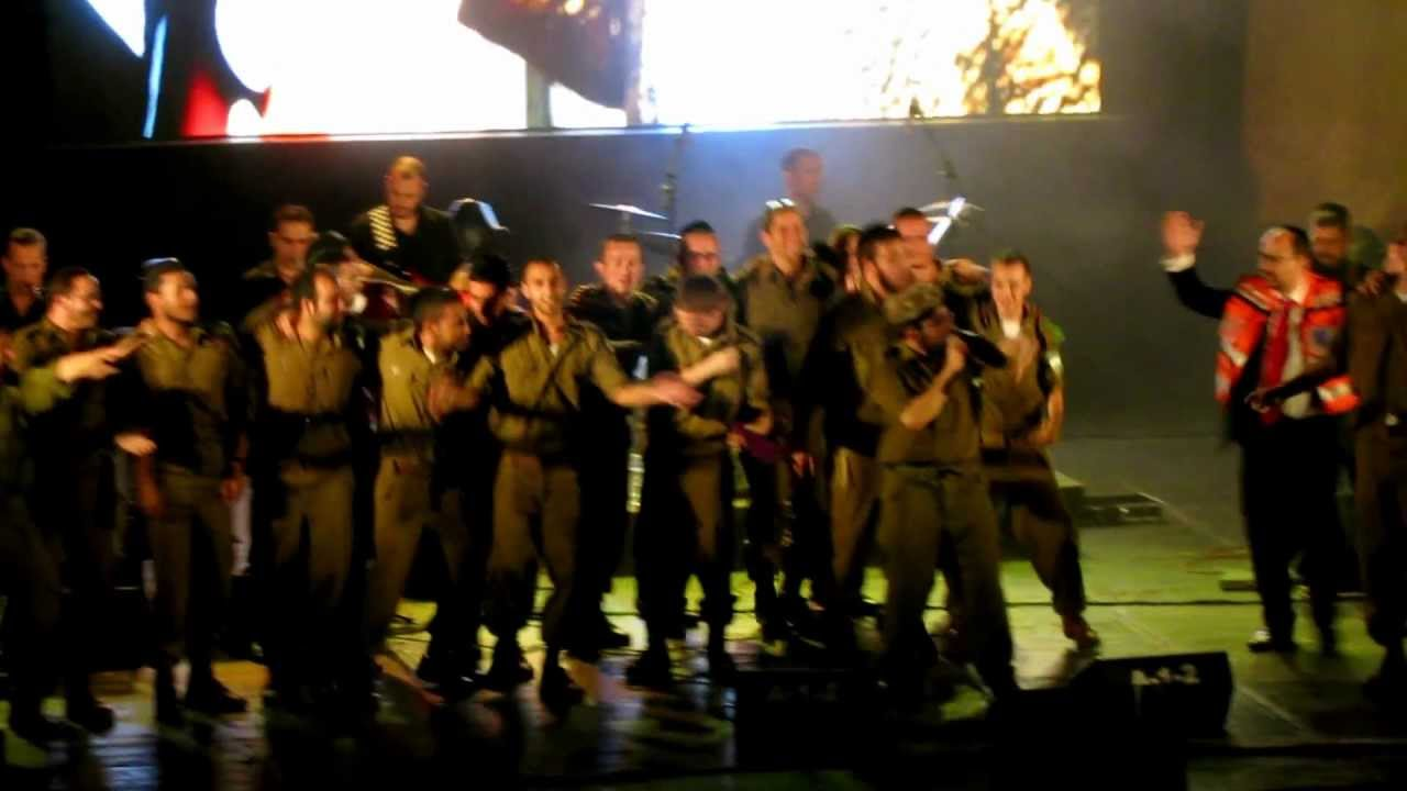 Lipa schmeltzer doing his mizrach dance with IDF soldiers on stage.