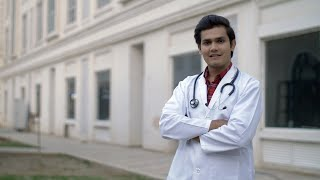 Attractive young man giving a toothy smile in doctor's uniform - profession concept