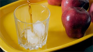 Pouring apple juice in a glass with ice