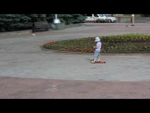 Маленький мальчик катается на самокате