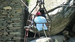 Tourists use man-powered cable trolley to cross stream in Kashmir