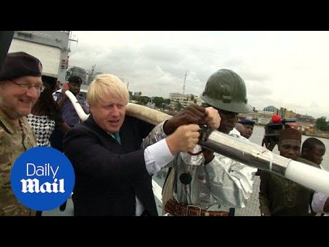 Boris holds fire hose during trip to meet Nigeria's navy - Daily Mail