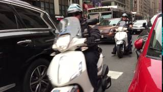 NYPD SCOOTER PATROL TEAM PATROLLING ON 7TH AVENUE IN THE MIDTOWN AREA OF MANHATTAN IN NEW YORK CITY.