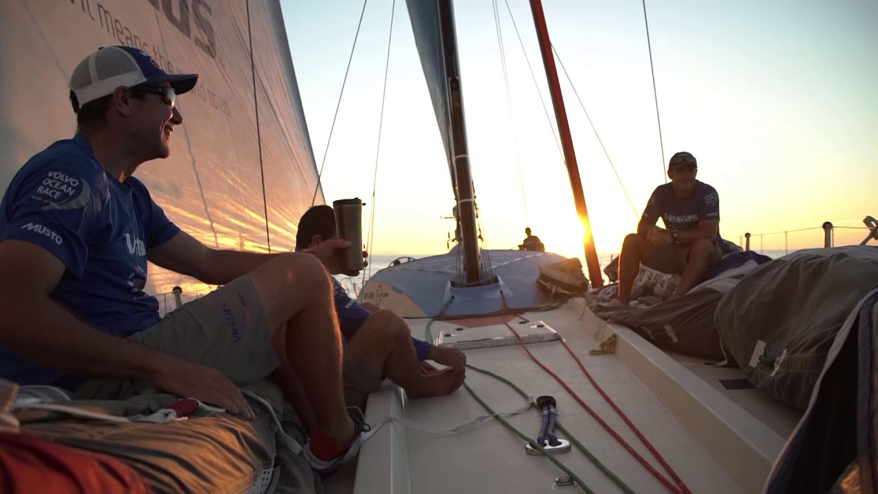 Bowsprit. Helm with sunset in light air. Crew on bow with SiFi laughing with sunset behind them. Mark trimming. All the other boats to leeward.