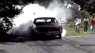 1965 GTO with open headers 455 and a stick doing a Smokey Burnout.