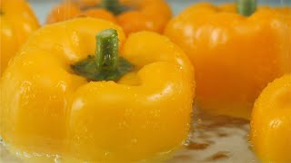 Pan shot of water droplets falling on yellow sweet pepper / capsicum