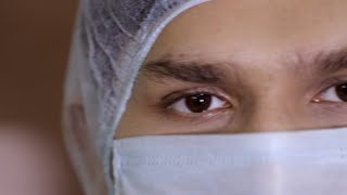 Pan shot of a young doctor in a protective face mask and hairnet - coronavirus concept