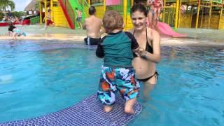 Мама купает годовалого малыша в бассейне