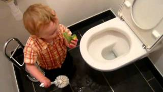 little 1 year old baby cleaning toilet
