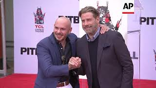 Travolta shows support for pal Pitbull at handprint ceremony in Hollywood