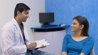 Footage of male doctor with a clipboard talking to a female patient at his clinic