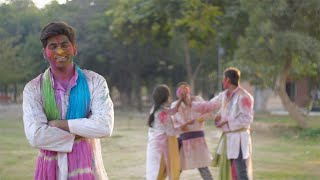 Handsome Indian guy having fun at the exciting color festival Holi - festive scene