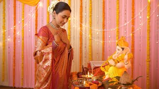 Hindu lady in traditional saree and jewelry performing the aarti and taking God's aashirwad / blessings