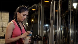 Indian female athlete in sportswear drinking protein shake - healthy drink concept