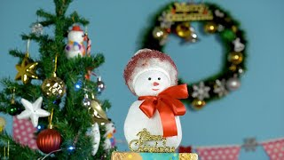Still shot of a smiling toy snowman with a colorful wreath hanging on the wall - festive scene