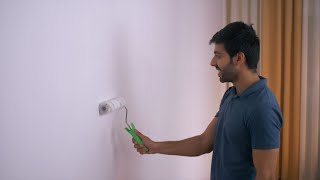 Close-up video of a young Indian boy painting walls of the room white with a roller
